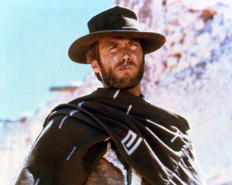 Clint Eastwood, US actor, smoking a cigar, wearing a brown hat and poncho in a publicity portrait issued for the film, 'A Fistful of Dollars', Spain, 1964. The Spaghetti western, directed by Sergio Leone (1929-1989), starred Eastwood as 'The Man with No Name' (Photo by Silver Screen Collection/Getty Images)